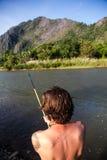 Fisherman. Young fisherman at shore of a river Royalty Free Stock Image