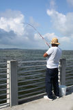 Fisherman. Rising the fish catch Royalty Free Stock Image
