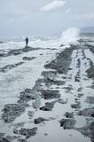 Fisherman. Lone fisherman standing on icy rocks casting into the breaking ocean waves Stock Photography