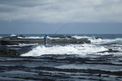 Fisherman. Lone fisherman casting into the ocean waves Stock Photos