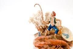 Fisherman. Model of fisherman standing on seashell Royalty Free Stock Photography