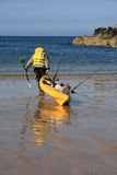 Fisherman. Porth Dafarch beach and cove with a fisherman going out on a kayak Royalty Free Stock Photo
