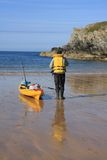 Fisherman. Porth Dafarch beach and cove with a fisherman going out on a kayak Royalty Free Stock Images