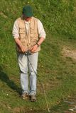 Fisherman. Standing by the waterside with his fishing rod royalty free stock photography