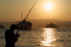 Fisherman. Silhouetted against a sunset from the Bosphorus royalty free stock photography