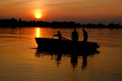 Fisherman. 3 fishermas in the boat at sunset sky Stock Photography