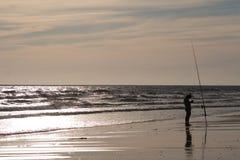 Fisherman. At beach in sunset stock image