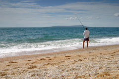 Fisherman. A man fishing on the beach Stock Photo