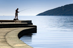 Fisherman. Lonely silhouette  of a fisherman standing. Hot summer day at city moorage Stock Photo