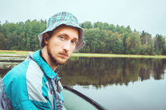 Fisherman in action. Bearded young man with panamku cap, from a boat, relaxing and fishing in  lake, outdoor weekend on. Fisherman in action. Bearded young man Royalty Free Stock Photo