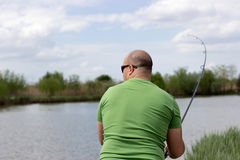 Fisherman in action, Fisherman holding rod in action.  Royalty Free Stock Photos