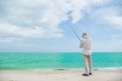 Fisherman action when fishing. On the beach Stock Photo