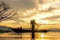 Fisherman action when fishing net on lake in the sunshine morning and silhouette fisherman outdoor on the boat,. Agriculture Thailand stock photography