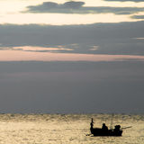 A fisherman alone in the sea. In the evening Royalty Free Stock Photography