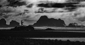 Solo fisherman on secluded beach royalty free stock photography