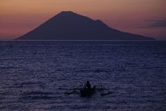 Fisherman Alone With Background Of Manado Tua Island Stock Image