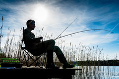 Fisherman or Angler at lake in Sunrise backlit Royalty Free Stock Images
