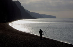Fisherman angling on beach. Silhouetted fisherman angling on beach at dusk or dawn; Sidmouth, Devon, England Royalty Free Stock Photography