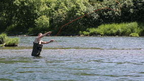 Fisherman angling on cold mountain river in summer season. BYSTRAYA RIVER, KAMCHATKA, RUSSIA - JULY 14, 2016: Summer fishing season - fisherman stands in cold stock video