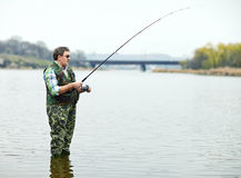Fisherman angling on the river. Mature fisherman angling on the river stock photo
