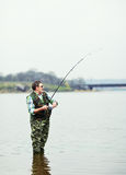 Fisherman angling on the river. Mature fisherman angling on the river Stock Images