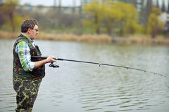 Fisherman angling on the river. Mature fisherman angling on the river royalty free stock photos