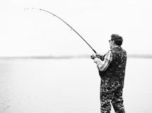 Fisherman angling on the river. Mature fisherman angling on the river.Back view.Monochrome Royalty Free Stock Photos
