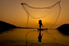Fisherman. Asian fisherman casting a net in nature river Royalty Free Stock Images