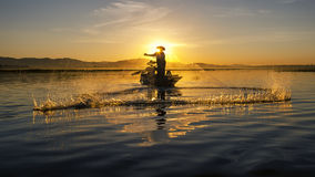 Fisherman of asian people at Lake in action when fishing stock photos