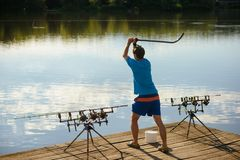 Fisherman attract fish with bait in river or lake. Man throw chum in water, fishing. Feeding, chumming, fishing, angling, catching fish. Hobby, sport, activity royalty free stock image