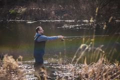 The fisherman throws a hook. Fisherman on the autumn background. The fisherman throws a hook Royalty Free Stock Photo