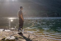 Fishing adventures, carp fishing. Angler on the shore of a lake. Fisherman in backlight. Carpfishing equipment, rod pod, bite alarms and fishing rods stock photo