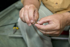 Fisherman baiting his hook. With a live cricket for freshwater fishing as he sits in a small boat with a close up view of his hands Stock Photos