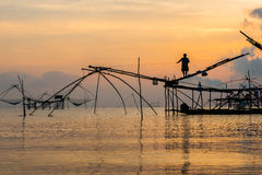 Fisherman on bamboo machinery in the morning Stock Photography