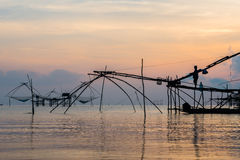 Fisherman on bamboo machinery in the morning Stock Image