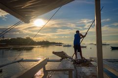 Fisherman on a banka, traditional filipino fishing boat at sunset, Cebu island The Philippines stock photography