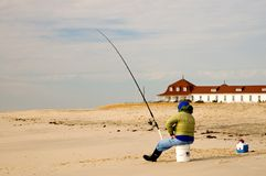 Fisherman on the Beach-1. A lone fisherman on the deserted beach, surf fishing on a cold, winter morning Royalty Free Stock Photo