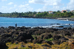 Fisherman at the beach. Flic en Flac Beach, Mauritius: man standing on rocks with his rod fishing in the sea Stock Image