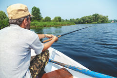 Fisherman with beard sitting in boat and holding fishing rod Royalty Free Stock Photography