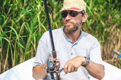 Fisherman with beard sitting in boat and holding fishing rod Stock Image