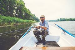 Fisherman with beard sitting in boat and holding fishing rod Royalty Free Stock Images