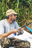 Fisherman with beard sitting in boat and holding fishing rod Stock Photos
