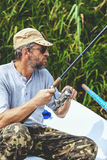 Fisherman with beard sitting in boat and holding fishing rod Stock Photography