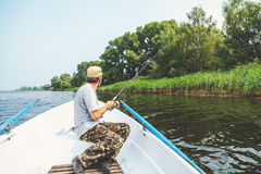 Fisherman with beard sitting in boat and holding fishing rod Royalty Free Stock Photo