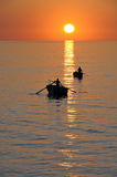 Fisherman on beautiful calm bay at sunrise royalty free stock image