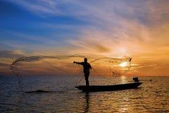 Fisherman with beautiful sunrise. Fisherman throwing his net on the boat with beautiful sunrise royalty free stock images
