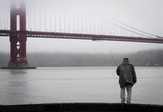 A fisherman below Golden Gate Bridge, San Francisco Royalty Free Stock Photo