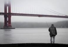 A fisherman below Golden Gate Bridge, San Francisco Royalty Free Stock Photo