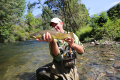 Fisherman with a big brown trout Royalty Free Stock Photos