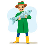 Fisherman Big Fish. Happy fisherman character holding big fish on his arms Royalty Free Stock Photo
